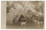 [Men standing before tent with rifles and dogs]