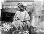 Paramaribo market scene. Woman seated with baskets of produce. 1922.